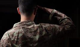 Ung soldat som saluterar anseende på svart bakgrund arkivbilder