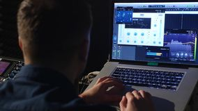 ung solid tekniker 4K i inspelningstudio genom att använda bärbara datorn på det blandande skrivbordet Royaltyfri Foto