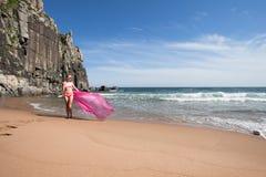 Ung spenslig kvinna på den steniga kusten för hav i en rosa baddräkt och ett rosa tyg som fladdrar i vinden Arkivbild
