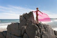 Ung spenslig kvinna på den steniga kusten för hav i en rosa baddräkt och ett rosa tyg som fladdrar i vinden Royaltyfria Bilder