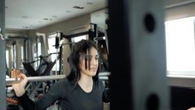 Ung sportig brunettflicka som får klar att göra övningar på ett satt med en skivstång Utbildning i idrottshallen arkivfilmer