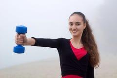 Ung sportig flicka som övar med dumbells under konditionworkou Royaltyfri Foto