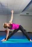 Ung sportig flicka som gör gymnastiska övningar i konditiongrupp Royaltyfri Bild