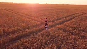 Ung sportig flickalöpare i vetefält arkivfilmer