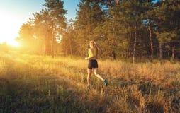 Ung sportig flickaspring på ett fält nära royaltyfri foto