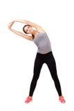 Ung sportig härlig kvinna som sträcker armar på sida Arkivbild