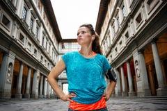Ung sportig kvinna för kondition framme av det Uffizi gallerit, Florence arkivfoton