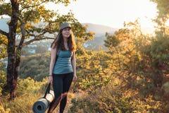 Ung sportig kvinna med yoga som är matt i hennes händer I bakgrunden, skogen och solnedgången Sportar, kondition och sunt livssti royaltyfri foto