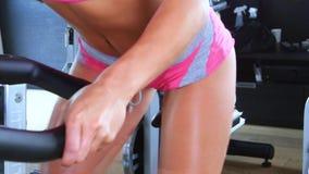 Ung sportig kvinna som är förlovad på en stationär cykel i idrottshallen arkivfilmer