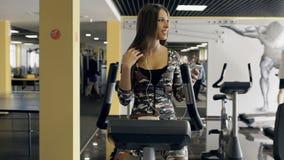 Ung sportig kvinna som är förlovad på en stationär cykel i idrottshallen och den lyssnande musiken i hörlurar arkivfilmer