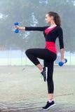 Ung sportig kvinna som övar med dumbells under utbildningsarbete Arkivfoto