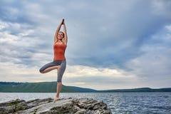 Ung sportig kvinna som gör olika varianter av yogapositionen på en stenig rivershore Royaltyfria Bilder