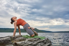 Ung sportig kvinna som gör olika varianter av yogapositionen på en stenig rivershore Royaltyfri Foto