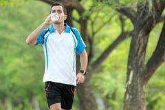 Ung sportig man som går, medan dricka en mineralvatten Arkivbild