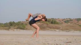 Ung sportig moder med litet göra för dotter som är gymnastiskt på stranden arkivfilmer