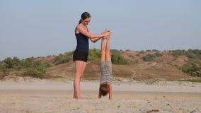 Ung sportig moder med litet göra för dotter som är gymnastiskt på stranden lager videofilmer