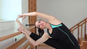 Ung sportive kvinna som sträcker ben i en idrottshall Nätt flicka som gör en balettövning arkivfilmer