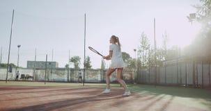 Ung sportivkvinna för blont hår som spelar den yrkesmässiga yttersidan för tennis på solig dag på tennisbanan arkivfilmer