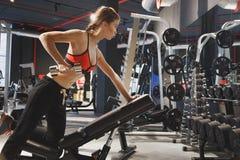 Ung sportkvinna som gör övningar med hantlar i idrottshallen arkivbilder