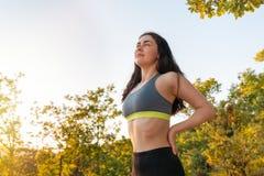 Ung sportkvinna som kopplas in i uppvärmning för sportar Begreppet av sporten, kondition och den sunda livsstilen arkivfoton