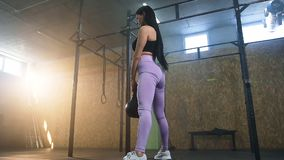 Ung sportkvinna som squatting med kettlebells i h arkivfilmer