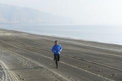 Ung sportman som bara kör på ökenstranden längs genomköraren för utbildning för havskust Arkivbild