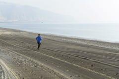 Ung sportman som bara kör på ökenstranden längs genomköraren för utbildning för havskust Royaltyfri Bild