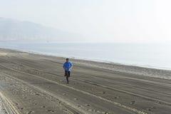Ung sportman som bara kör på ökenstranden längs genomköraren för utbildning för havskust Arkivfoton