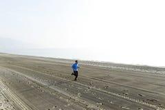 Ung sportman som bara kör på ökenstranden längs genomköraren för utbildning för havskust Royaltyfri Fotografi