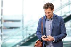 Ung stads- yrkesmässig man som använder den smarta telefonen