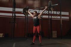 Ung stark kvinna som rymmer tung skivstångfast utgift Sportkvinna som gör crossfitövning arkivfoto