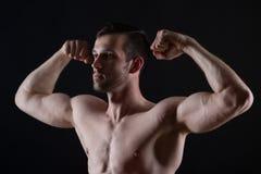 Ung stark man med muskler på svart bakgrund royaltyfri fotografi