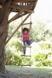 Ung stege för pojkeklättringrep till treehousen arkivbild