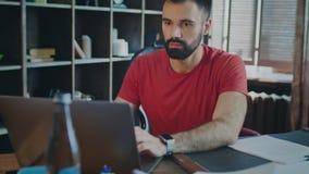 Ung stilfull affärsman som arbetar på bärbara datorn med koncentrerat uttryck på framsida arkivfilmer