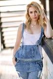Ung stilfull blond flicka i grov bomullstvilloveraller utomhus med naturligt dagsljus, en solig dag Royaltyfri Bild