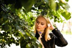 Ung stilfull blond kvinna som är utomhus- bak trädet royaltyfria foton