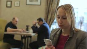 Ung stilfull blond kvinna som tar selfiefotoet med mobiltelefonen i kafé stock video