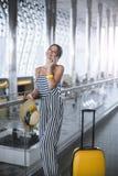 Ung stilfull Caucasian kvinna på flygplatsen med en resväska och en sugrörhatt royaltyfria bilder