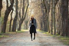 Ung stilfull flicka med buköverkanten som går på en aveny royaltyfria foton