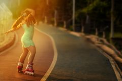Ung stilfull flicka, rullskridskor och dans under solnedg?ng arkivfoto