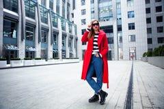 Ung stilfull flicka som förbigår Windows Bärande trendiga exponeringsglas och ett rött lag Abstrakt se till sidan begrepp av st Royaltyfria Bilder