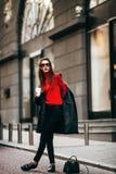 Ung stilfull flicka som förbigår Windows Bärande trendiga exponeringsglas och ett svart lag Håller kaffe Arkivfoto