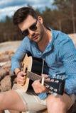 ung stilfull gitarrist, i att spela för solglasögon som är akustiskt royaltyfri bild