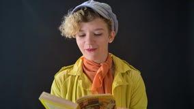 Ung stilfull kvinna i basker med den lockiga läseboken för blont hår som isoleras på svart bakgrund, kvinnlig i gult omslag lager videofilmer