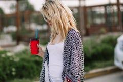 Ung stilfull kvinna i en stadsgata nära en vit bil Fotografering för Bildbyråer