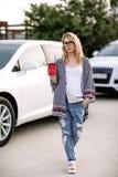 Ung stilfull kvinna i en stadsgata nära en vit bil Arkivbild