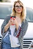 Ung stilfull kvinna i en stadsgata nära en vit bil Arkivbilder
