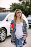 Ung stilfull kvinna i en stadsgata nära en vit bil Royaltyfri Bild
