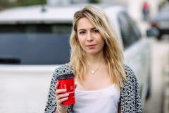Ung stilfull kvinna i en stadsgata nära en vit bil Arkivfoton