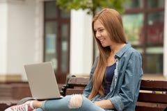 Ung stilfull kvinna med en bärbar dator Fotografering för Bildbyråer